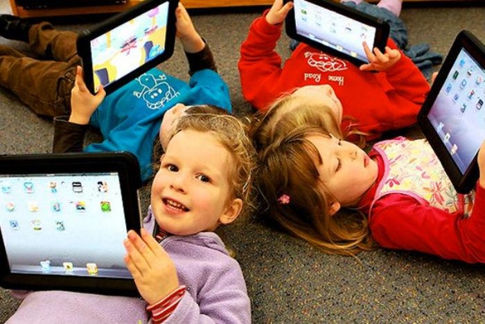 Дети играют на планшете.