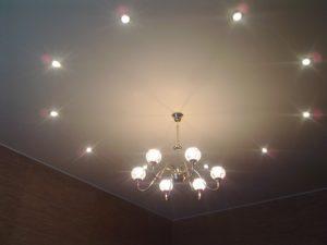Точечные светильники и люста на натяжном потолке.