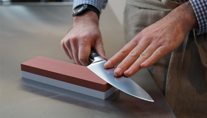 Мужчина точит нож на точильном камне