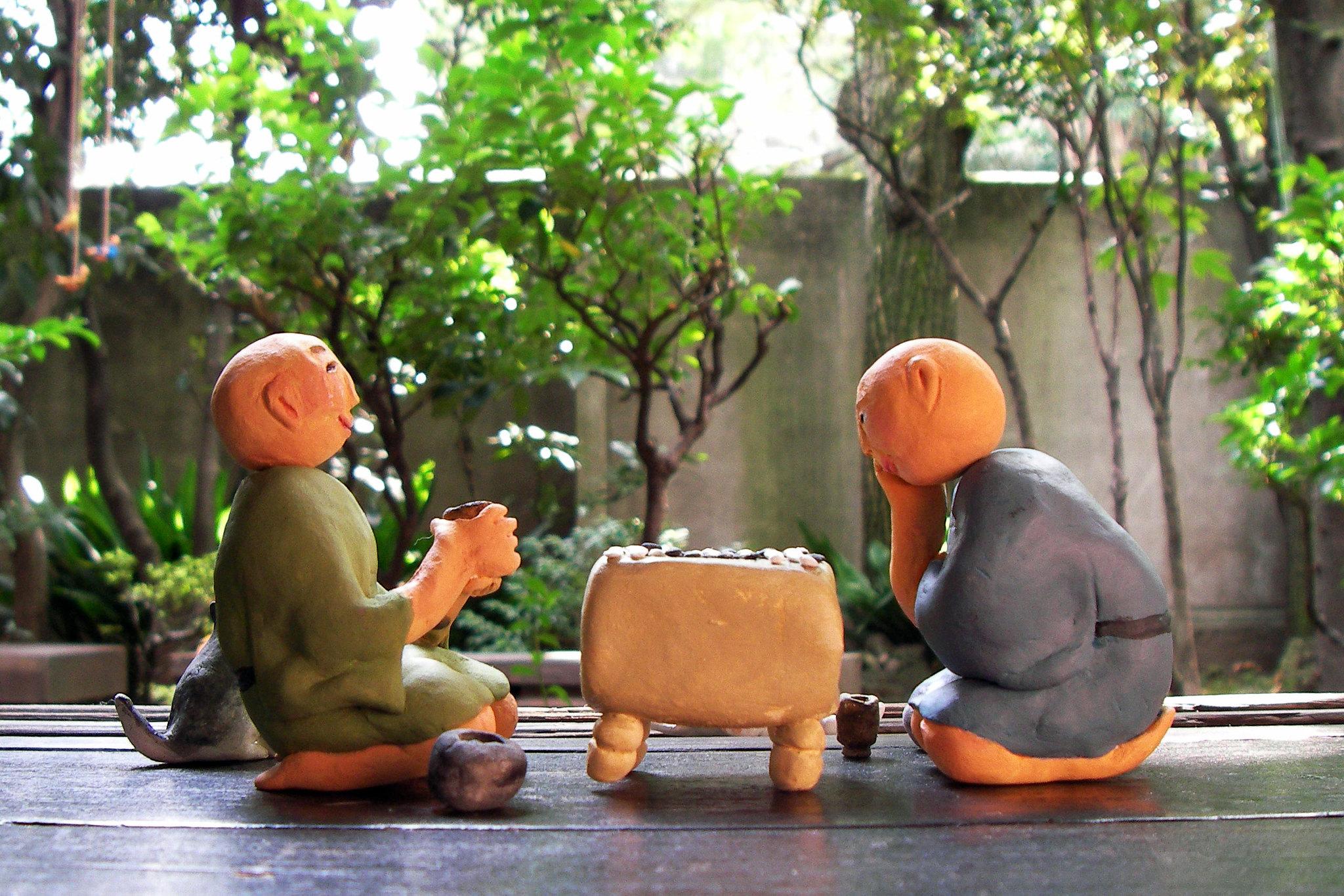 Два человечка из глины играют в настольную игру