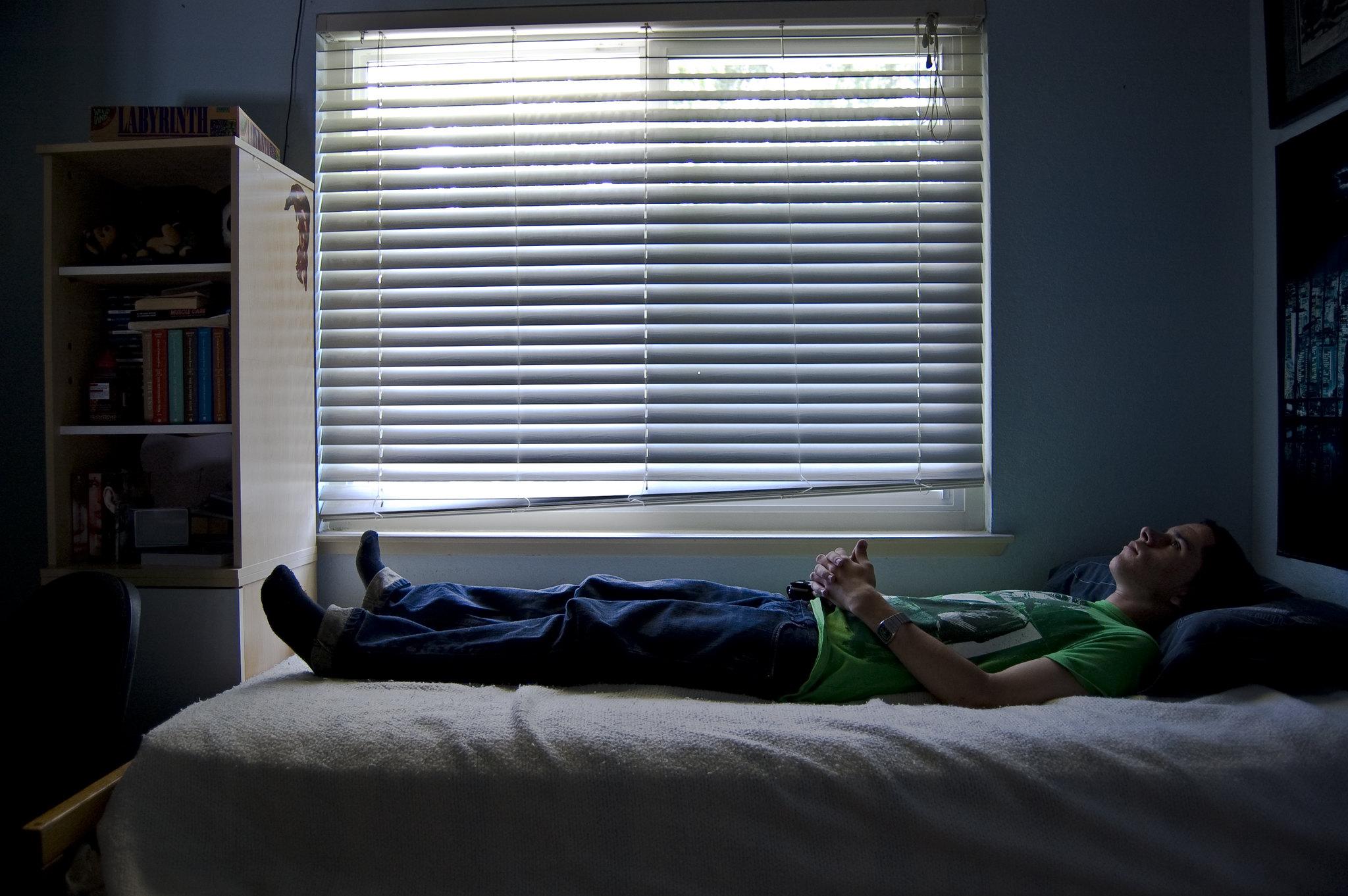 Грустный парень лежит на кровати